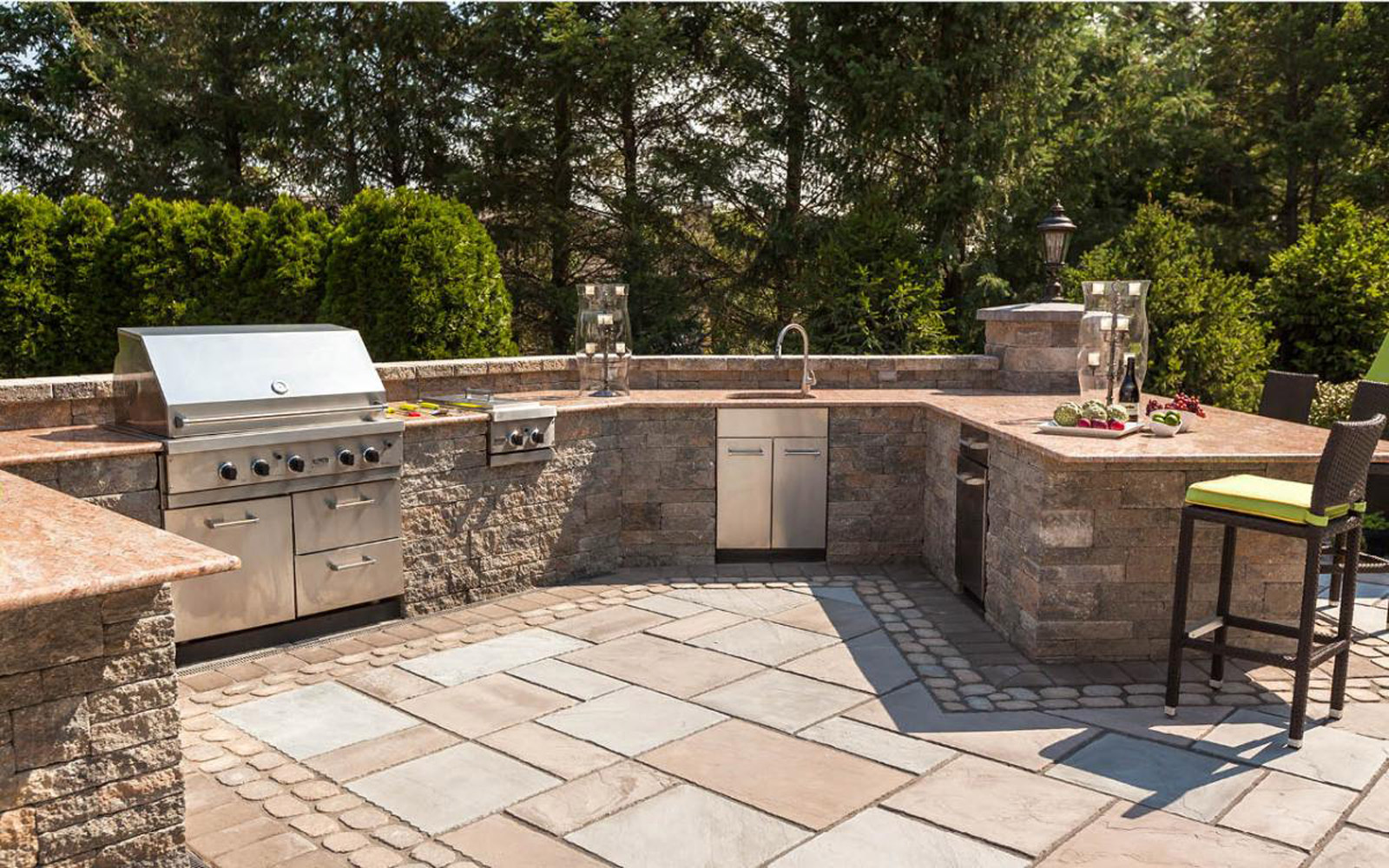 outdoor kitchen with stone walls flagstone patio and granite countertops