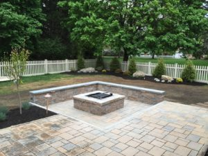 paver patio with fireplace and stone wall