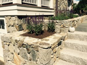 Stone retaining wall with stone walkway