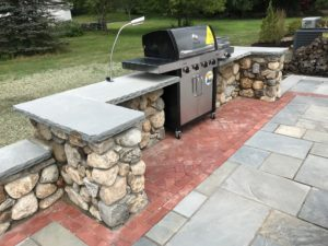 patio with stone outdoor kitchen and walls