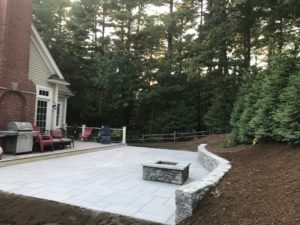 stone patio with curved stone wall and a matching stone fire pit for bbq